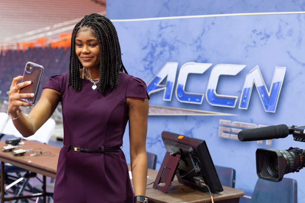 A student taking a selfie in front of the ACC Network logo